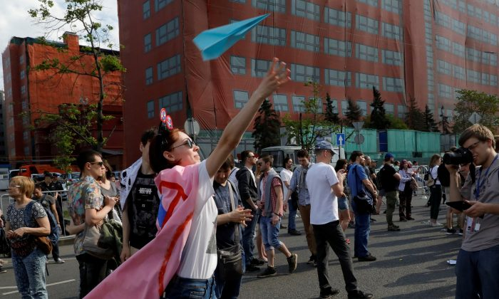 A youth releases a paper plane, symbol of Telegram messenger, during a rally in protest against a court decision to block it because it violated Russian regulations, in Moscow on May 13, 2018. (Reuters/Tatyana Makeyeva/File Photo)