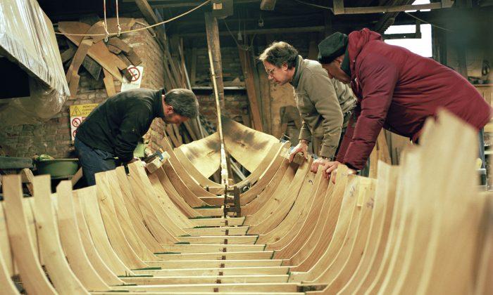 Workers at Domenico Tramontin e Figli inspect the gondola's ribbed frame. (Susanna Pozzoli/Michelangelo Foundation)