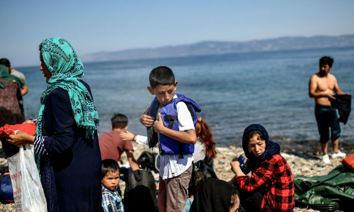 Migrants from Afghanistan arrive after crossing the Aegean Sea from Turkey with a dinghy on the Greek Mediterranean island of Lesbos on August 6, 2018. (Aris Messinis/AFP/Getty Images)