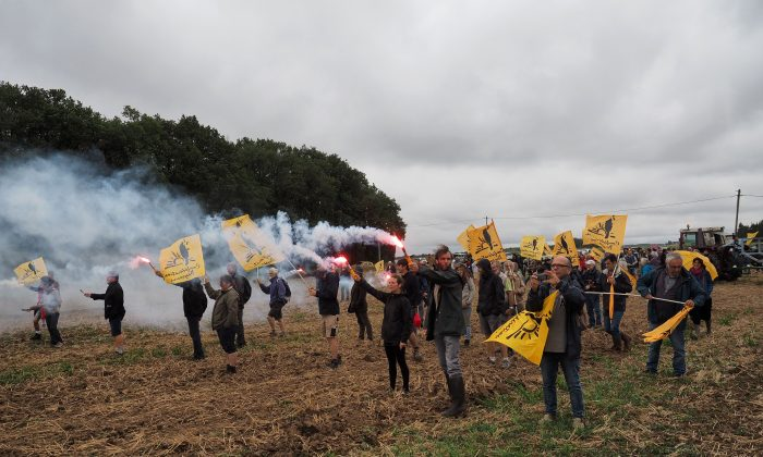 Members of French farmers union La Confederation Paysanne walk with flares as they occupy fields belonging to Chinese farmers, during a demonstration against 'land grabbing' by Chinese investors, in Murs, France. on Aug. 29, 2018. (Guillame Souvant/AFP/Getty Images)