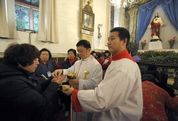 Chinese worshippers attend a Holy Communion during Christmas Mass at a Catholic church in Beijing on December 24, 2009. About 15 million Protestants and five million Catholics worship at official churches, according to China's official data. (Liu Jin/AFP/Getty Images)