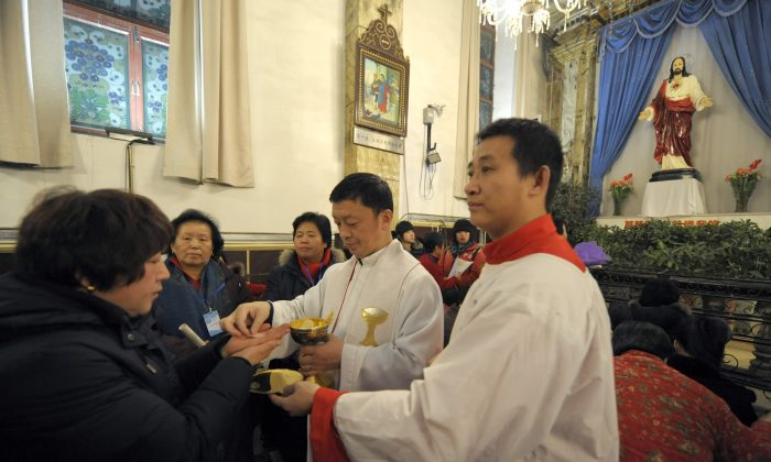 Chinese worshippers attend a holy communion during Christmas Mass at a Catholic church in Beijing on Dec. 24, 2009. (Liu Jin/AFP/Getty Images)