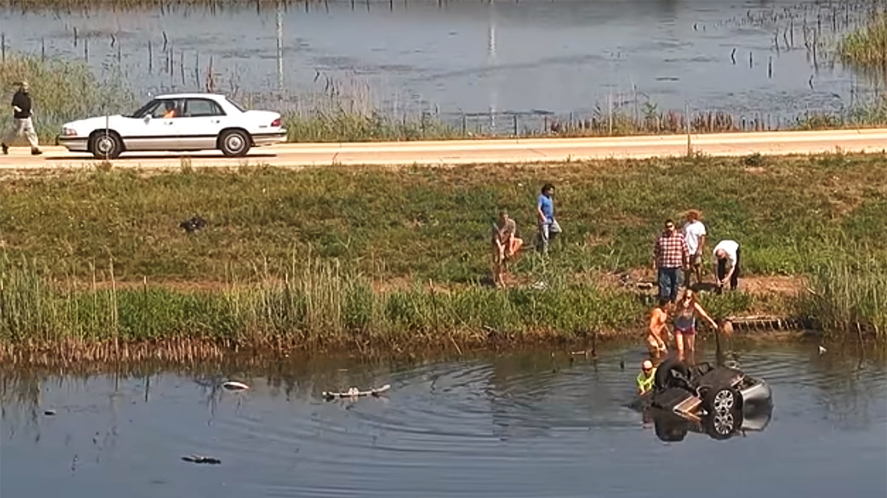 Bystanders flock to where a woman's car slid into a retention pond.