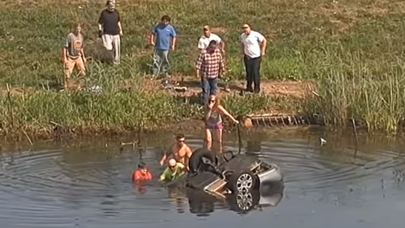 Two men pull the victim out of the car