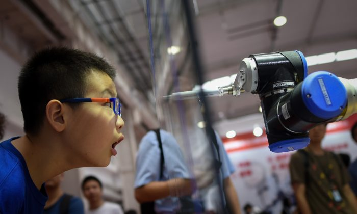 A boy looks at a robot arm at the 2018 World Robot Conference in Beijing on Aug. 15, 2018. (Wang Zhao/AFP/Getty Images)