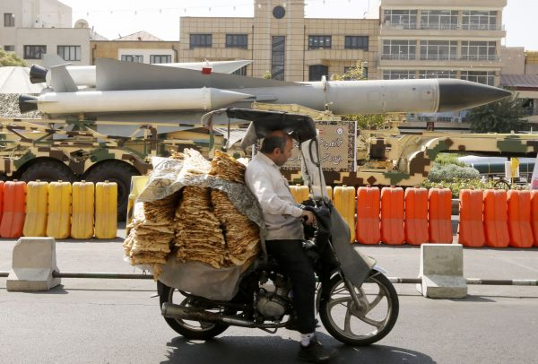 A man rides past missiles in Iran