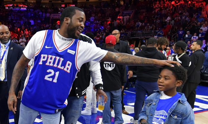 Entertainer Meek Mill stands with his son Papi at halftime during the game between the Miami Heat and Philadelphia 76ers at Wells Fargo Center in Philadelphia on April 24, 2018. (Drew Hallowell/Getty Images)