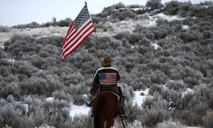 A man carries an American flag as he rides his horse near Burns, Ore., on Jan. 7, 2016. (Justin Sullivan/Getty Images)