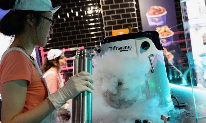 An employee creates ice cream at the Nitrogenie ice cream store using liquid nitrogen in Paris on Aug. 4, 2016. (Bertrand Guay/AFP/Getty Images)