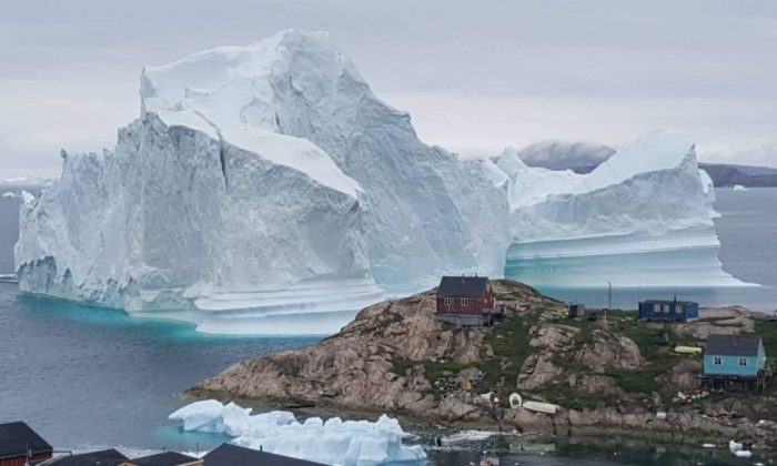 An iceberg behind houses and buildings outside the village of Innarsuit, an island settlement in the Avannaata municipality in northwestern Greenland. (Magnus Kristensen/AFP/Getty Images)