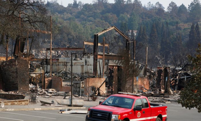 A firefighting crew drives pass a business destroyed in wildfire that tore through Santa Rosa, California, on Oct. 15, 2017. (Reuters/Jim Urquhart)