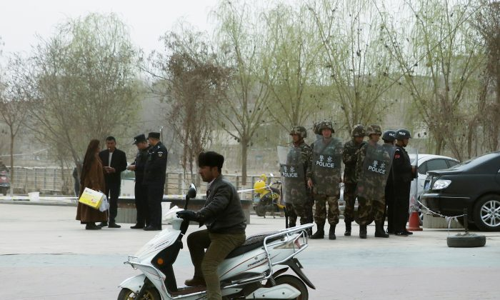 FILE PHOTO: Police officers check the identity cards of a people as security forces keep watch in a street in Kashgar, Xinjiang Uighur Autonomous Region, China, March 24, 2017.  REUTERS/Thomas Peter