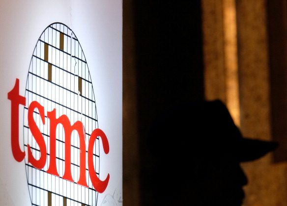 A security staff stands next to a logo of the Taiwan Semiconductor Manufacturing Corp., during the investors conference in Taipei on July 16, 2014. (Sam Yeh/AFP/Getty Images)