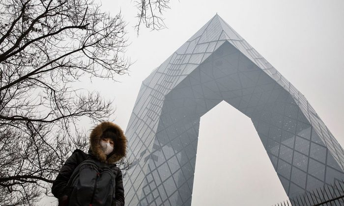 A Chinese woman wears a mask to protect against pollution as she passes the CCTV building in Beijing on Dec. 8, 2015. (Kevin Frayer/Getty Images)