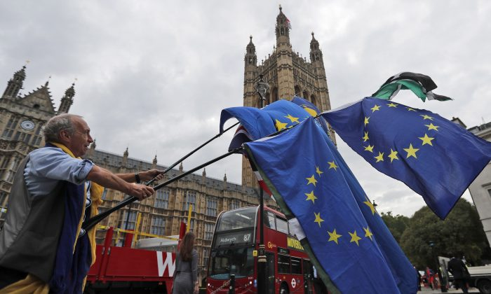 A protestor waves EU flags in front of the Houses of Parliament in London on Sept. 4. (AP Photo/Frank Augstein)