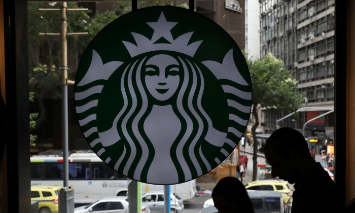 Customers pass by the logo of an American coffee company Starbucks inside a coffee shop in Rio de Janeiro, Brazil, on Aug. 15, 2018. (Pilar Olivares/Reuters)