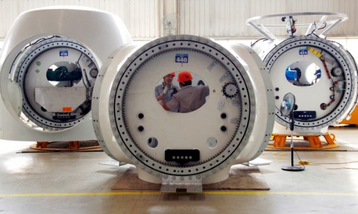 FILE PHOTO: Workers stand inside a newly painted wind turbine tower as a fan blows it dry, in the assembly workshop of the Guodian United Power Technology Company at the city of Baoding, Hebei Province June 20, 2011.  REUTERS/David Gray/File Photo