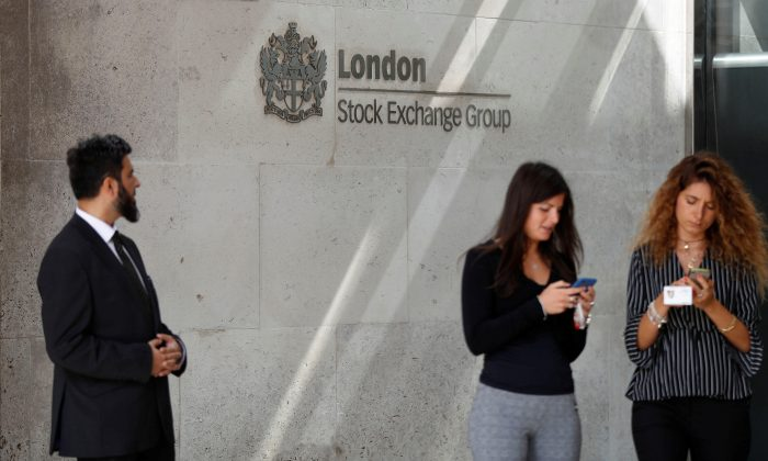 FILE PHOTO - People check their mobile phones as they stand outside the entrance of the London Stock Exchange in London, Britain. Aug 23, 2018. REUTERS/Peter Nicholls