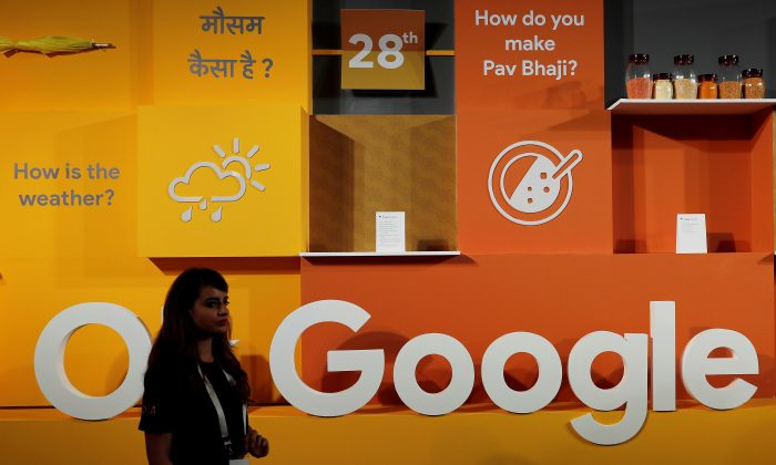 A woman walks past the logo of Google during an event in New Delhi, India, August 28, 2018. (Reuters/Adnan Abidi).