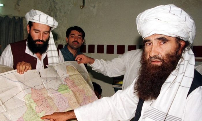 File photo: Jalaluddin Haqqani (R), the Taliban's Minister for Tribal Affairs, points to a map of Afghanistan during a visit to Islamabad, Pakistan, October 19, 2001 while his son Naziruddin (L) looks on. Reuters/File Photo
