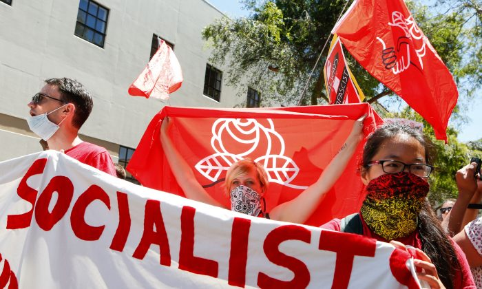 Democratic Socialists of America counter protesters holding signs and flags as they march, protesting a rally on Aug. 5, 2018 in downtown Berkeley, California. (Amy Osborne/AFP/Getty Images)