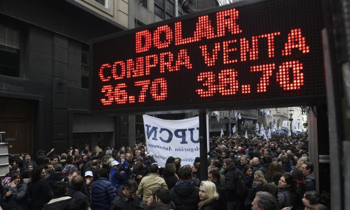 "A buy-sell board of a bureau de exchange is seen as outsourced government workers protest against layoffs in Buenos Aires's downtown, on September 3, 2018. - Argentina's president Mauricio Macri announced austerity measures, including the elimination of government ministries and stiff taxes on exports to reduce budget deficits and stabilize the economy in Buenos Aires. The Argentinian peso has lost half its value against the dollar since January. A first $15 billion tranche of an IMF loan has largely gone to propping up the peso in recent months. Argentina's Central Bank hiked its baseline interest rate to 60 percent last week in a further bid to stabilize the currency (Photo by Juan Mabromata / AFP) / The erroneous mention[s] appearing in the metadata of this photo by Juan Mabromata has been modified in AFP systems in the following manner: ""A buy-sell board of a bureau de exchange is seen as outsourced government workers protest against layoffs in Buenos Aires's downtown, on September 3, 2018"" instead of ""Demonstrators protesting against the economic policies of the government walk past in front of a bureau de exchange in Buenos Aires, on September 3, 2018"". Please immediately remove the erroneous mention from all your online services and delete them from your servers. If you have been authorized by AFP to distribute them to third parties, please ensure that the same actions are carried out by them. Failure to promptly comply with these instructions will entail liability on your part for any continued or post notification usage. Therefore we thank you very much for all your attention and prompt action. We are sorry for the inconvenience this notification may cause and remain at your disposal for any further information you may require.        (Photo credit should read JUAN MABROMATA/AFP/Getty Images)"