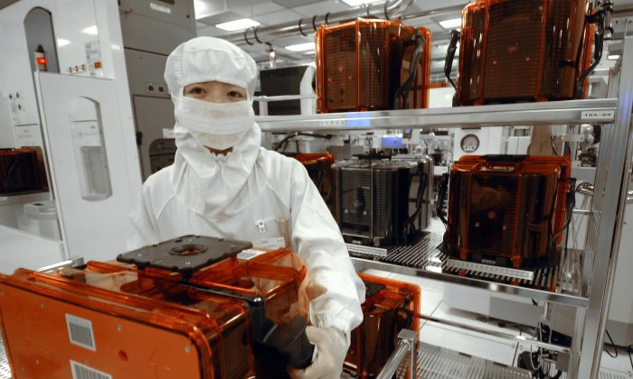 An engineer holds a wafer pod at a wafer factory in Tainan Science Park, southern Taiwan, on April 28, 2006. (Sam Yeh/AFP/Getty Images)