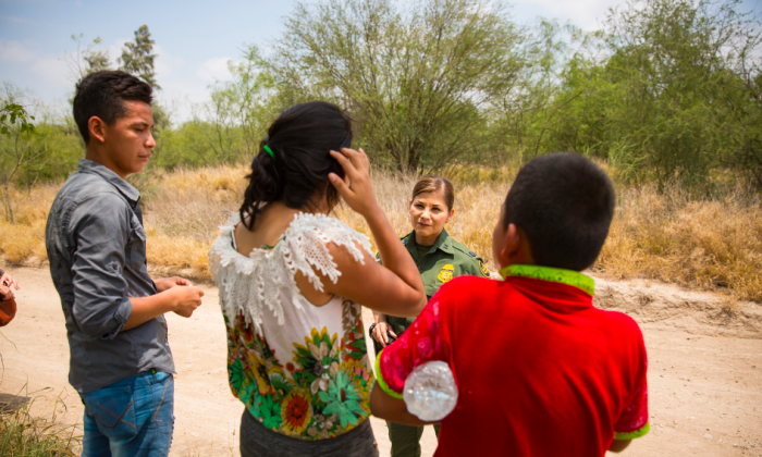 Supervisory Border Patrol agent Marlene Castro speaks to a group of unaccompanied minors who just crossed the Rio Grande illegally from Mexico into the United States, in Hidalgo County, Texas, on May 26, 2017. (Benjamin Chasteen/The Epoch Times)