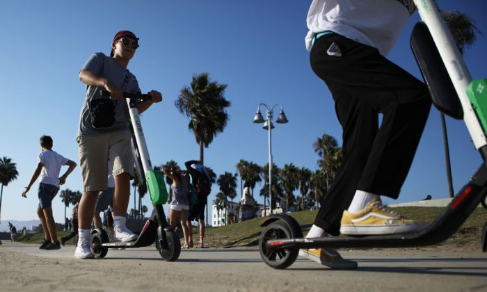 People ride Lime shared dockless electric scooters along Venice Beach in Los Angeles, California on Aug. 13, 2018. (Mario Tama/Getty Images)