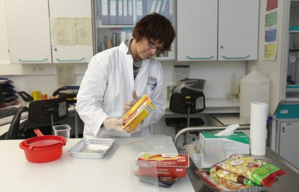 A laboratory technician checks for possible horsemeat in a lasagne