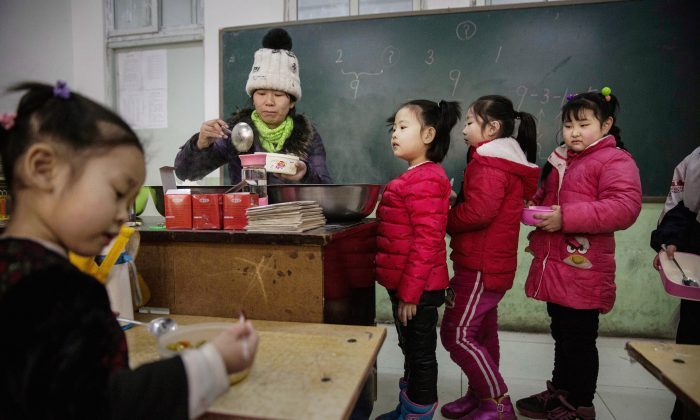 Chinese students wait in line for lunch in a classroom at a school in Beijing on December 18, 2015. (Kevin Frayer/Getty Images)