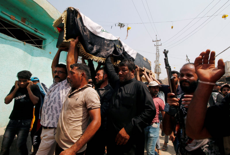 Mourners carry the coffin of a protester