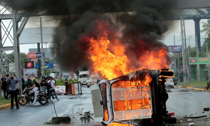File photo: People take pictures of a burning police car during a protest against Nicaraguan President Daniel Ortega's government in Managua, Nicaragua September 2, 2018. (Reuters/Oswaldo Rivas/File Photo)