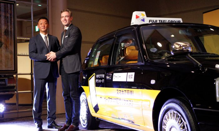 Uber Japan General Manager Tom White and Fuji Taxi Group President Hisashi Umemura (L) shake hands during a news conference in Nagoya, Japan on Sept. 6, 2018. (Reuters/Yoshiyasu Shida)
