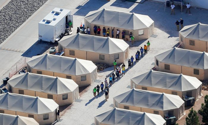 "Immigrant children now housed in a tent encampment under the new ""zero tolerance"" policy by the Trump administration are shown walking in single file at the facility near the Mexican border in Tornillo, Texas, U.S., June 19, 2018.        REUTERS/Mike Blake/File Photo"