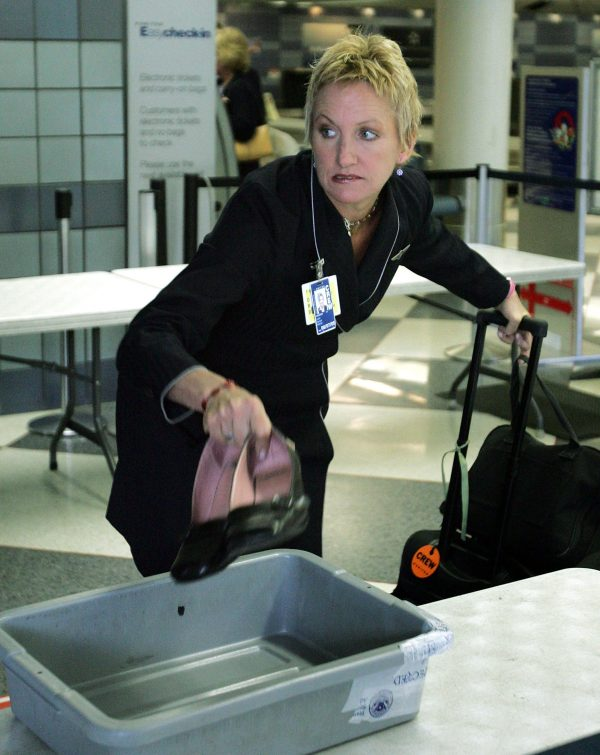 A flight attendant drops her shoes into a plastic tray as she prepares to pass through a security