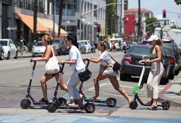 Women ride scooters in Santa Monica in California