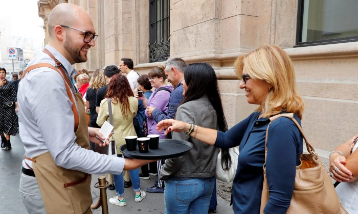 A staff member of Starbucks Reserve Roastery offers coffee to the customers in line at the entrance, during the opening day in downtown Milan, Italy, Sept. 7, 2018. (Reuters/Stefano Rellandini)