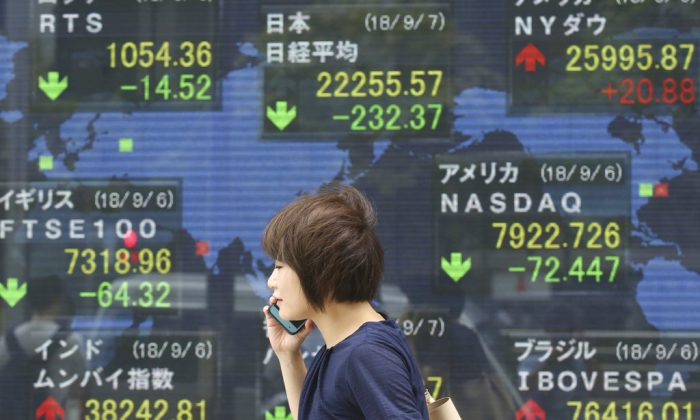 A woman walks by an electronic stock board of a securities firm in Tokyo on Sept. 7, 2018. (Koji Sasahara/AP)