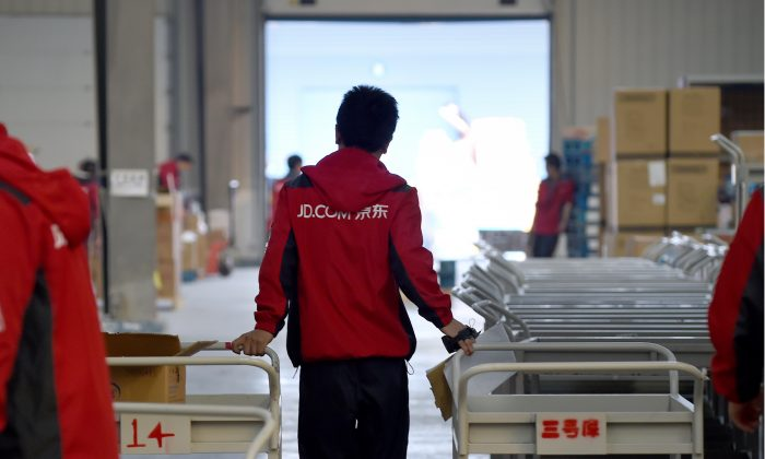 A worker at online retailer JD.com pulling a trolley at a warehouse in Langfang City, Hebei Province, on Nov. 3, 2015. (Wang Zhao/AFP/Getty Images)