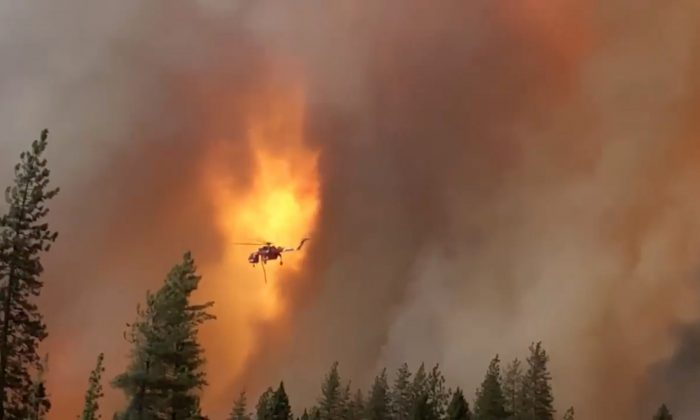 A helicopter drops water on a forest fire in Shasta County in California, on September 5, 2018. (California Highway Patrol/via Reuters)