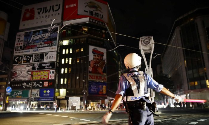 A police officer is seen during blackout after a powerful earthquake hit the area at a cross-point in Sapporo, Japan in this photo taken by Kyodo Sept. 6, 2018. (Kyodo/via Reuters)