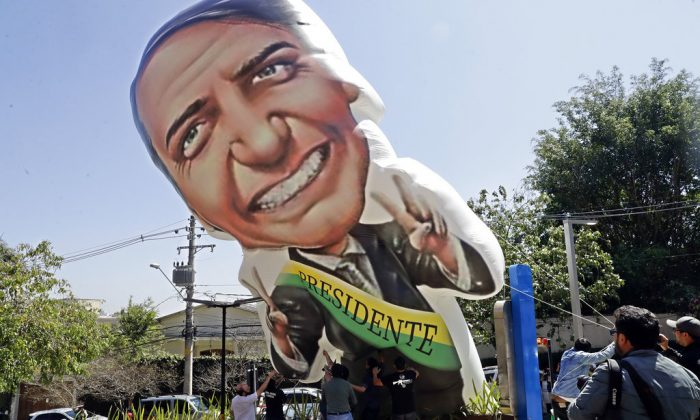 Supporters of Brazilian presidential candidate Jair Bolsonaro, who was stabbed during a campaign event, inflate a large doll depicting him, outside the Albert Einstein Hospital, where the candidate was transferred, in Sao Paulo, Brazil on Sept. 7, 2018. (Andre Penner/AP Photo)