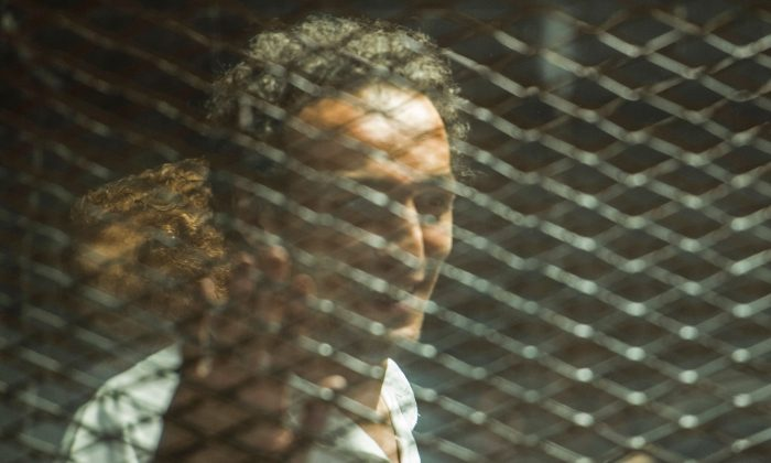 Egyptian photojournalist Mahmoud Abu Zeid, known as Shawkan, looks out from his soundproof glass dock during his trial in the capital Cairo, on September 8, 2018. (Mohamed el-Shahed/ AFP/Getty Images)