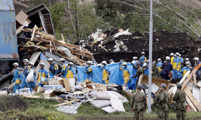 Police officers and members of the Japan Self-Defense Forces (JSDF) carry a missing person found from an area damaged by a landslide caused by an earthquake in Atsuma town, Hokkaido, northern Japan, on Sept. 8, 2018. (Mandatory credit Kyodo/via Reuters)