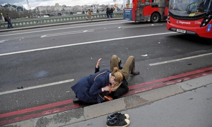 A woman assists an injured person after the attack on Westminster Bridge in London, on March 22, 2017. (Reuters/Toby Melville/File photo)