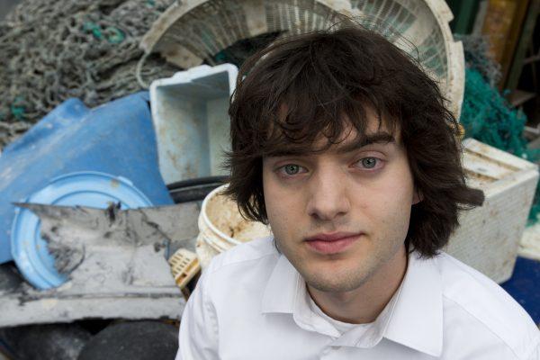 Boyan Slat poses next to a pile of plastic