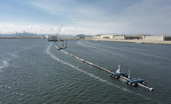 A long floating boom that will be used to corral plastic litter in the Pacific Ocean is assembled