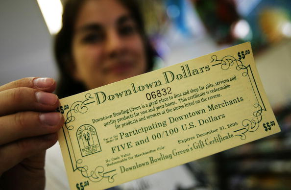"""Checkout girl Abby Feick holds """"Downtown Dollars,"""" a local business incentive promotion, at the Ben Franklin general store May 10, 2005 in Bowling Green, Ohio. (Chris Hondros/Getty Images)"""