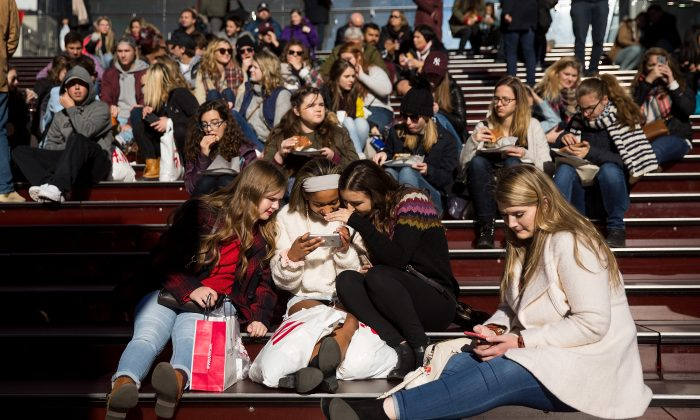 A group of teens look at a photograph they took on a smartphone in Times Square in New York City on Dec. 1, 2017. (Drew Angerer/Getty Images)